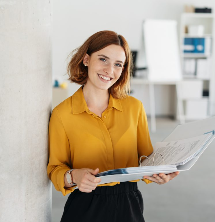 Attractive young office worker holding a large open binder as she looks at the camera with a sweet friendly smile